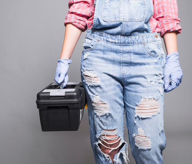 Woman in overall holding tool box