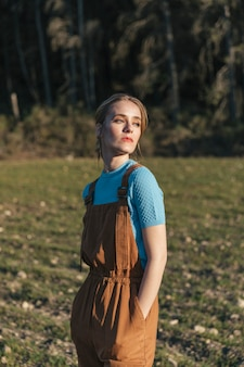 Woman in overall looking sideways