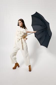 Woman in overalls brown boots fashion open umbrella rain protection