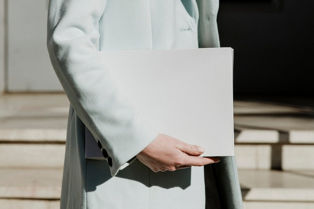 Woman in an overcoat carrying a white box in front of a building
