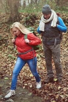 森の中の小さな川を乗り越える女性