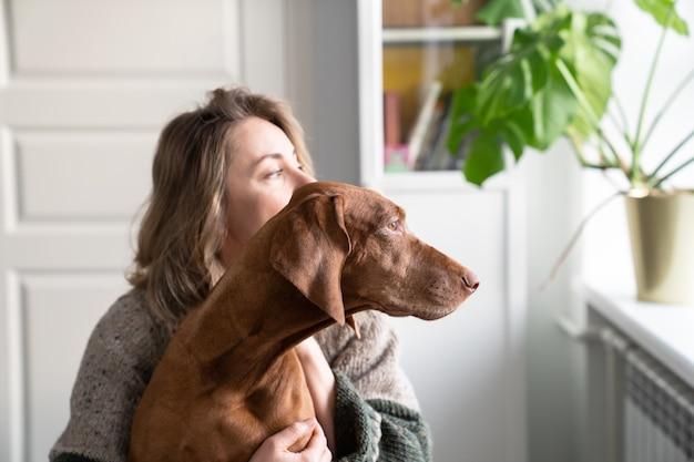 여자 소유자와 그녀의 vizsla 개가 함께 창턱에 앉아 창을 통해보고. 애완 동물에 대한 사랑. 달콤한 집, 실제 생활 개념.