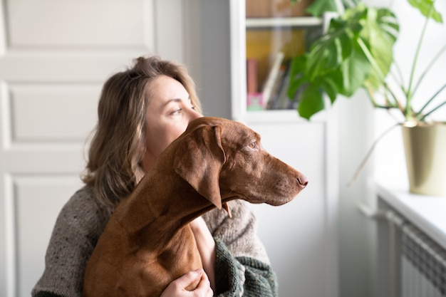 Woman owner and her vizsla dog sitting together on windowsill, looking through the window. love for pet. sweet home, real life concept.