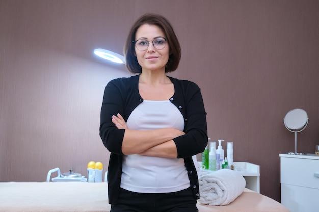 Женщина-владелец салона красоты, позирует, космический массажный стол и оборудование