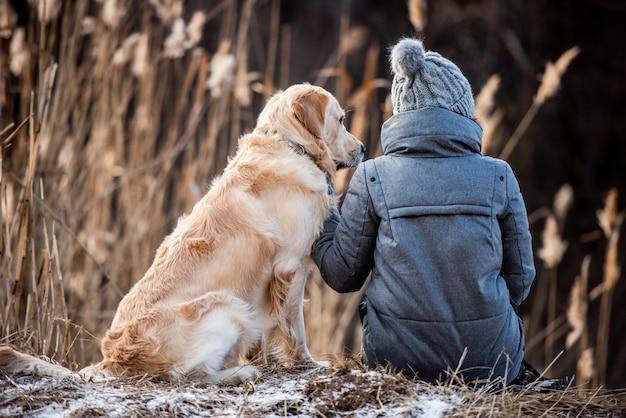 Владелец женщины сидит на земле с собакой золотистого ретривера во время прогулки на свежем воздухе ранней весной ...