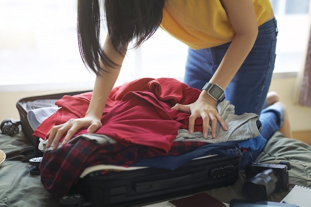 Woman pack clothes in suitcase bag on bed