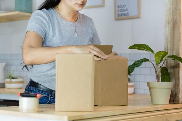 配送用パッケージを梱包する女性