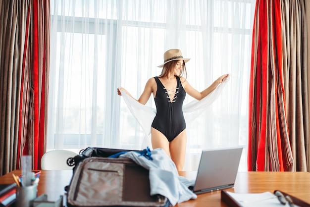 Женщина пакует чемодан, думая о путешествии.