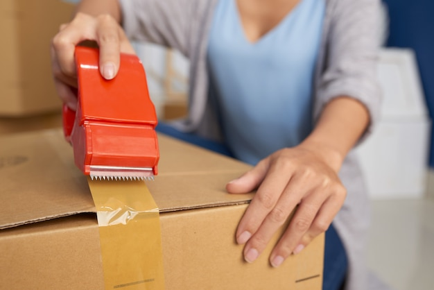 Woman packing box with tape