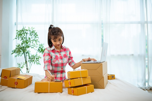 Woman packing boxes for prepare shipping to customer