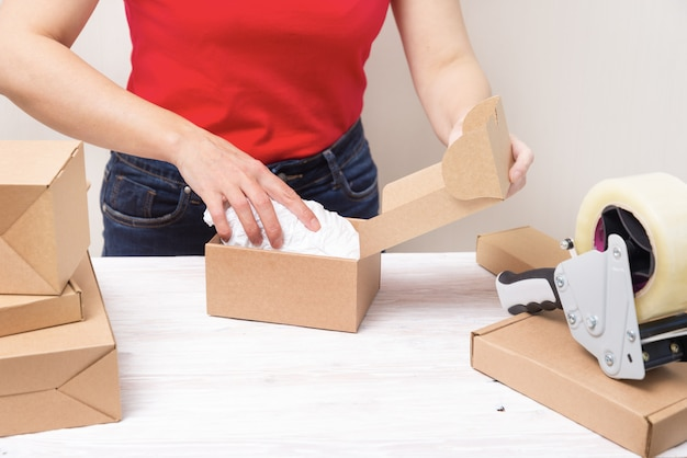 Woman packing cardboard boxes , picking and puttind products