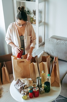 Woman packing food for donation in paper bag