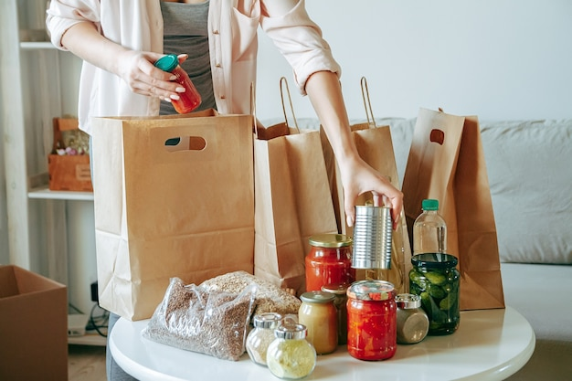 종이 봉지에 기부를 위해 음식을 포장하는 여자