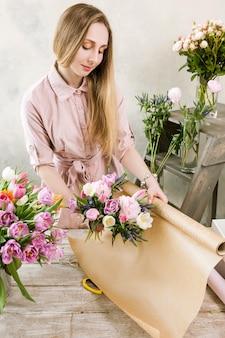 핑크 봄 꽃다발 평면도를 포장하는 여자. 젊은 플로리스트는 플로리스트 리가 나무 배경에 워크샵에서 조립하게