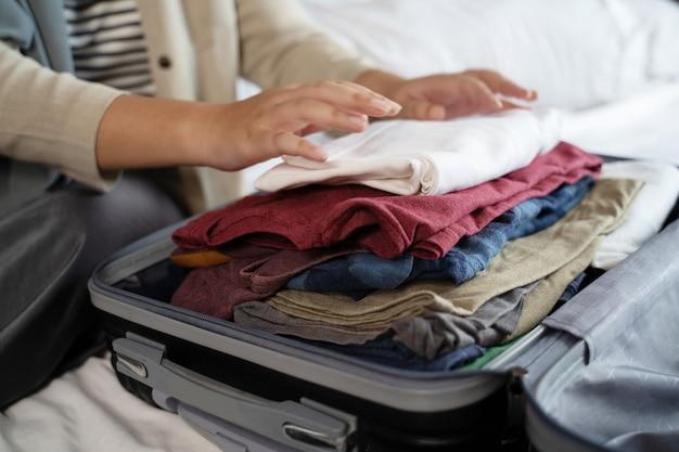 いくつかの服を梱包する女性