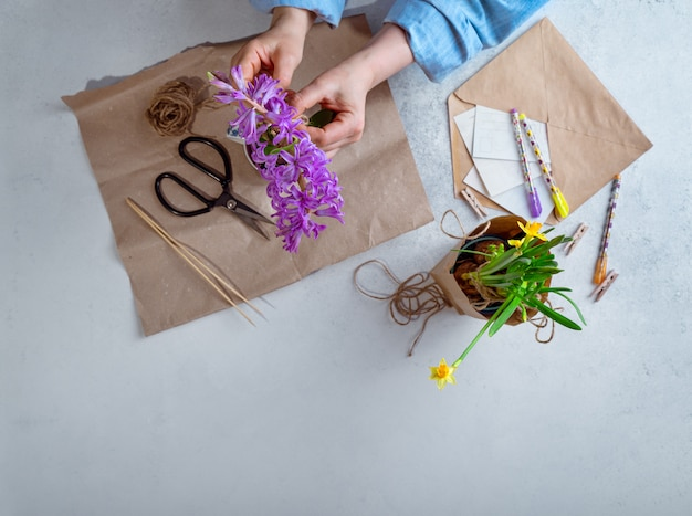 Woman packing spring potted flowers as gifts, top view, with copy space