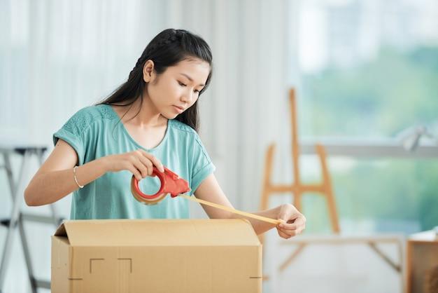 箱を梱包する女性