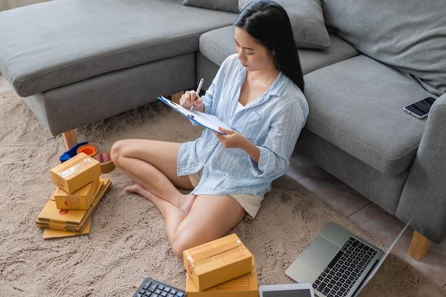 女性はオンラインで商品を梱包して販売しています。小規模なビジネス。在宅勤務のコンセプトを販売するhome.smeからの仕事。グループ。