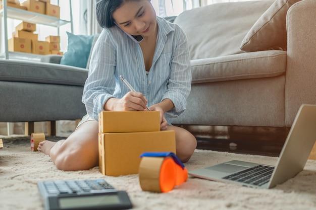 Женщина упаковывает и продает товары в интернете. малый бизнес. работа от home.sme продажа работы на дому концепции. группа.
