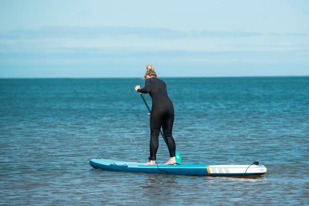 Woman paddleboarding full shot