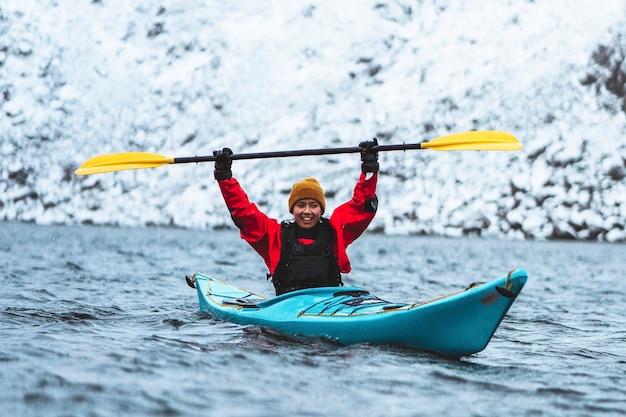 Женщина плывет на байдарке на лофотенских островах, норвегия