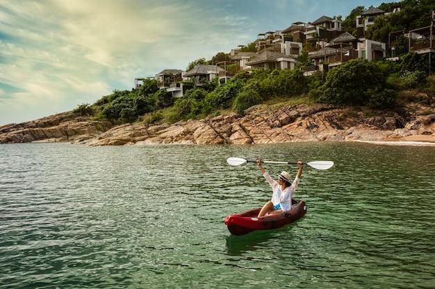 Женщина плывет на байдарке, исследуя спокойную тропическую бухту с известняковыми горами на мальдивах, деревенском острове самуи, таиланд.