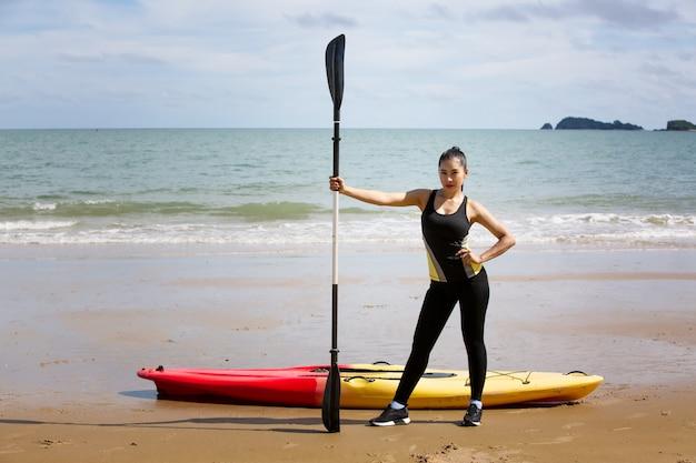 Woman paddling a kayak by the tropical beach. kayaking tour in phuket, thailand