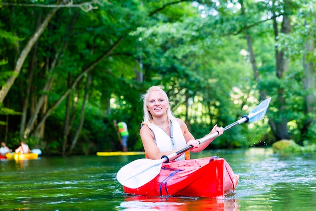 Woman paddling with canoe on forest river in summer