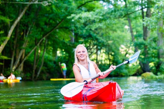 Женщина, гребля на каноэ по лесной реке летом