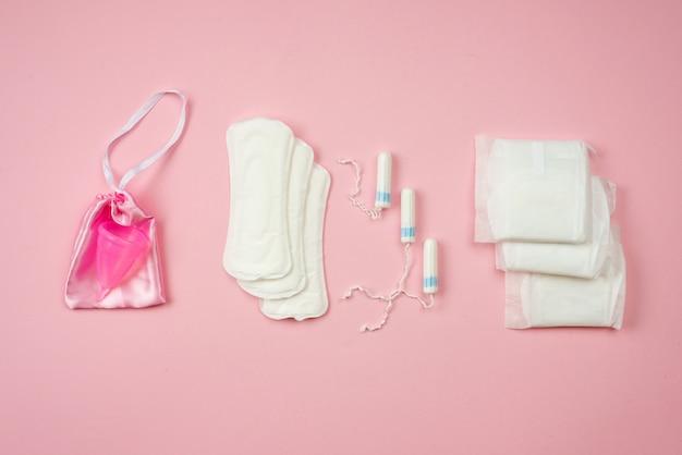 Женщина колодки, тампоны и менструальные чашки лежа изолированы. концепция женской защиты