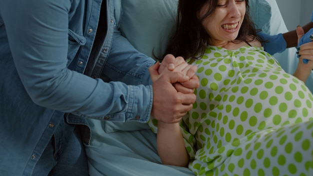 Woman in pain from childbirth holding hands with husband
