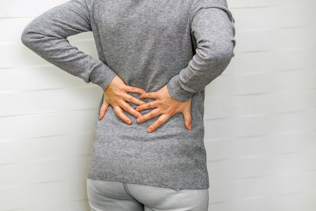 Woman, pain at lower back. health care concept.