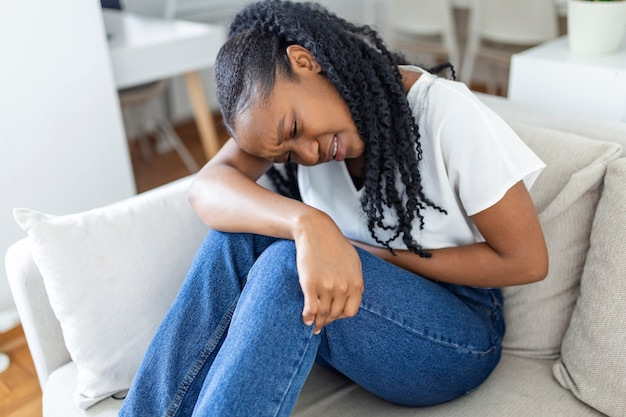Woman in painful expression holding hands against belly suffering menstrual period pain, lying sad on home bed, having tummy cramp in female health concept