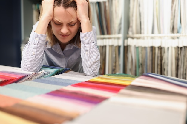 Woman painfully thinks about which fabric to choose in store how to choose the right color in