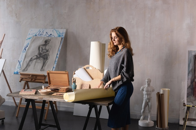 Woman painter holding a brush and palette with oil paints in her hand, standing in front of an empty canvas, drawing.