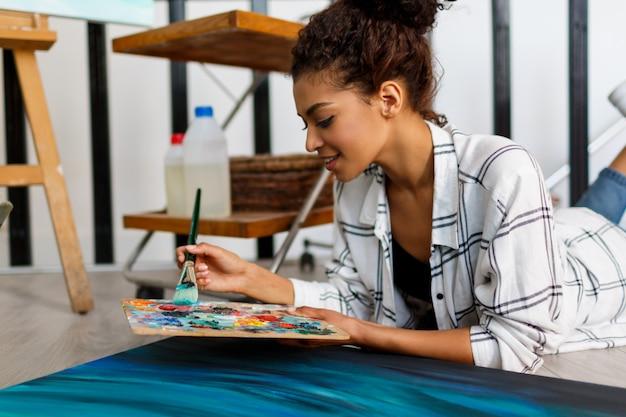 La pittrice si trova sul pavimento vicino alla tela e al disegno. interno dello studio dell'artista. forniture per il disegno, colori ad olio, pennelli per artisti, tela, cornice. concetto creativo.