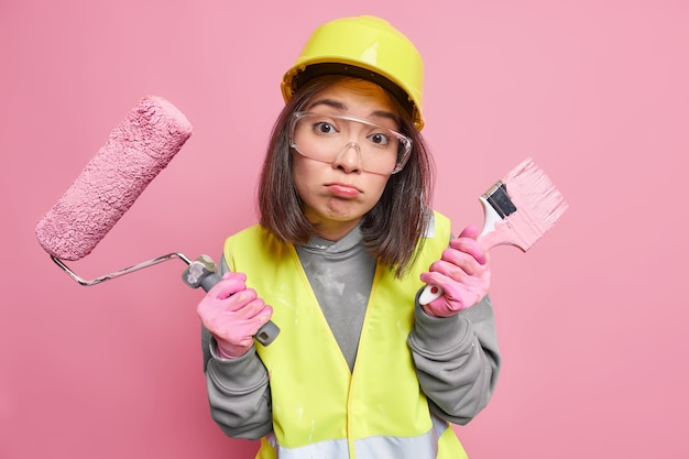 Woman painter looks unhappily purses lips holds painting brush and roller dressed in uniform going to redecorate house