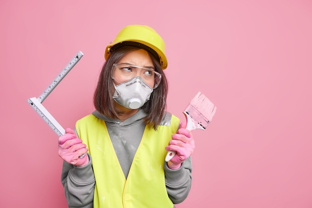여성 화가나 재건 작업자는 줄자로 집 벽을 측정하고 아파트에서 무언가를 다시 장식할 건축 도구를 들고 있습니다. 집 및 수리 개념