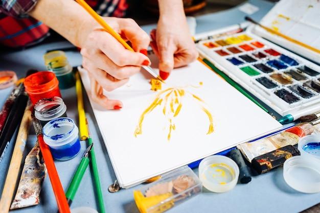 Художник-женщина рисует яркими красками и кистью на белой бумаге