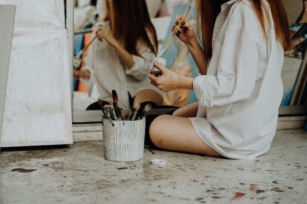 Woman painter sitting on the floor in front of mirror and drawing. art studio interior. drawing supplies, oil paints, artist brushes