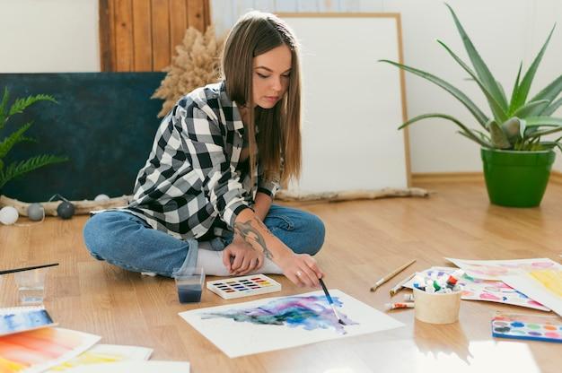 床に座っている女性画家