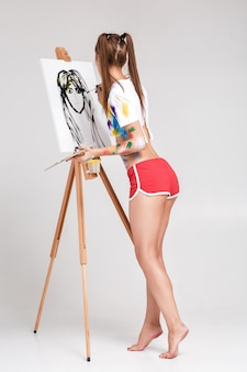 캔버스에 다채로운 페인트로 더러워진 여성 화가