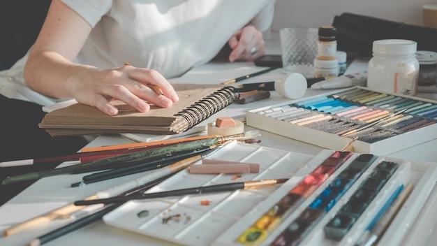 Женщина рисует картину кистью. учимся рисовать дома.