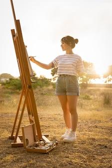 Donna che dipinge su tela fuori nella natura
