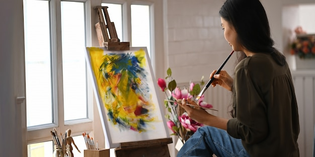 Woman painting on canvas with paintbrush while sitting at the chair