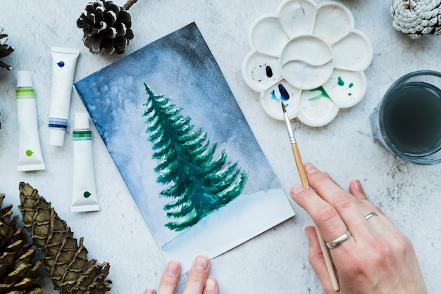 Woman painting the christmas tree with paint brush