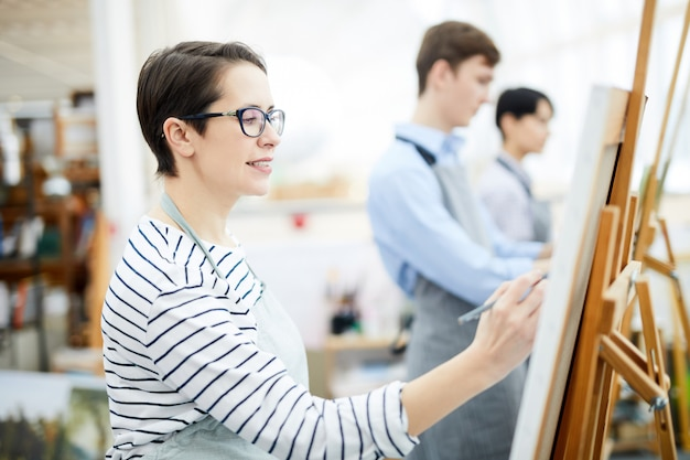 Woman painting on easel