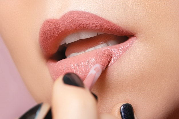 Woman painting her lips with liquid lipstick, close up.