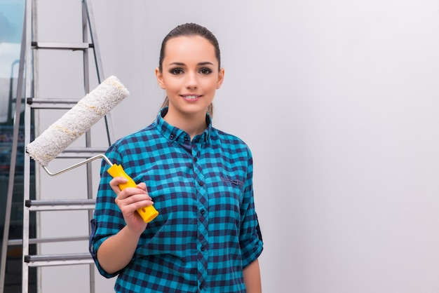 Woman painting house in diy concept