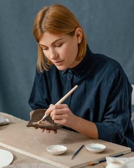 Colpo medio della foglia della pittura della donna